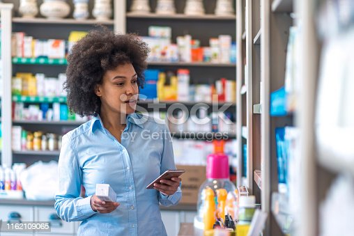Young woman choosing medicine standing with phone in the pharmacy store. Photo of mixed race woman using cell phone searching internet and reading drug or pill label and prescription medications. Health care concept. Serious woman standing in drugstore with her smartphone in hand.