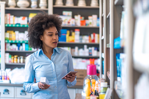 Woman buying cosmetic in pharmacy store. Woman uses smart phone while in pharmacy