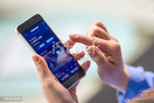 istock Woman buying cryptocurrency through mobile phone app 1054923550