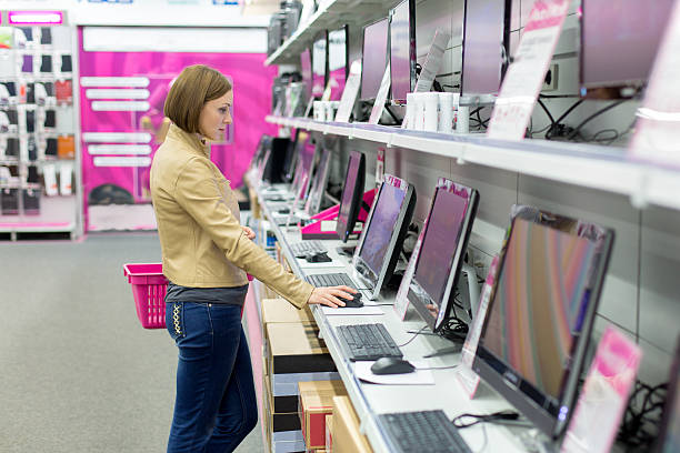 woman buying desktop in store stock photo