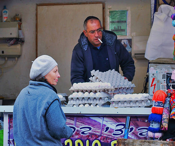 Woman buying eggs from smoking shop owner, Jerusalem, Israel stock photo