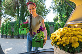 Young cheerful woman arranging flower crates in her car trunk
