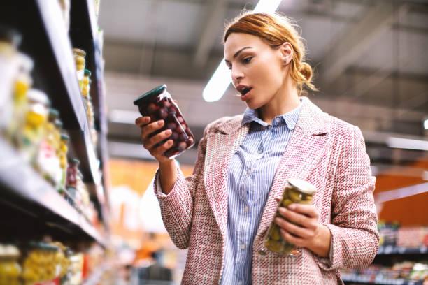 vrouw koopt voedsel bij supermarkt. - ingrediënt stockfoto's en -beelden