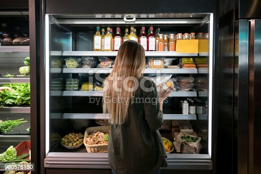 Woman buying food at the supermarket and reading a label on a product - lifestyle concepts