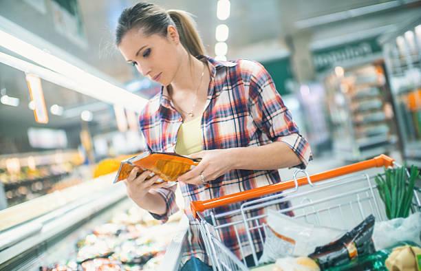 mulher comprar comida no supermercado. - comida congelada - fotografias e filmes do acervo