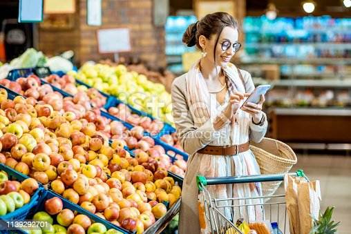 Young woman looking on the shopping list using smartphone while shopping food in the supermarket