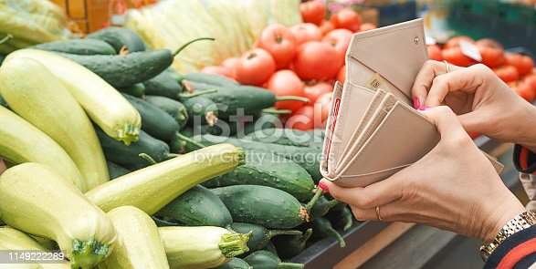 istock Woman buying fresh and organic fruits and vegetables at the green market or farmer agricultural market . 1149222289