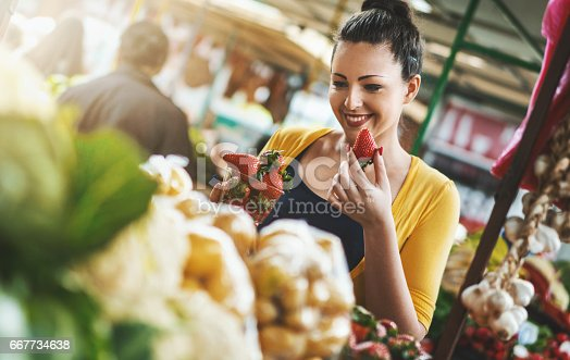 Closeup front view of late 20's attractive woman choosing some fruit at local food market.She's holding a pack of strawberries and smiling. She's wearing a nice casual yellow blouse.