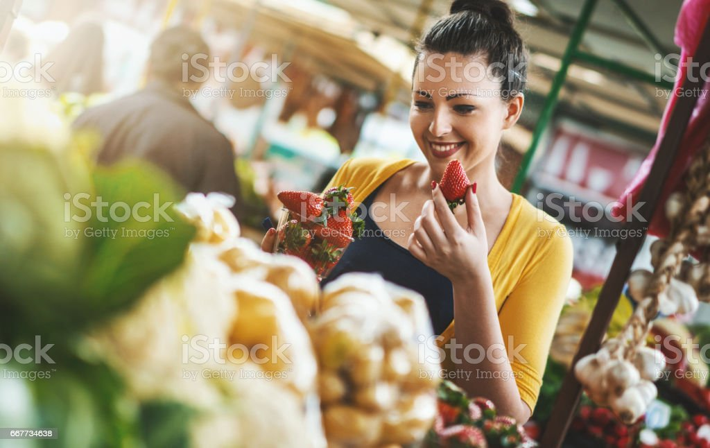 Woman buying fresh fruits and vegetables. stock photo