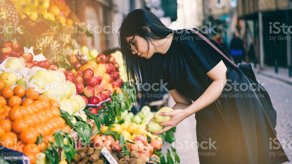 ストリート マーケットで果物を買う女 ストックフォト