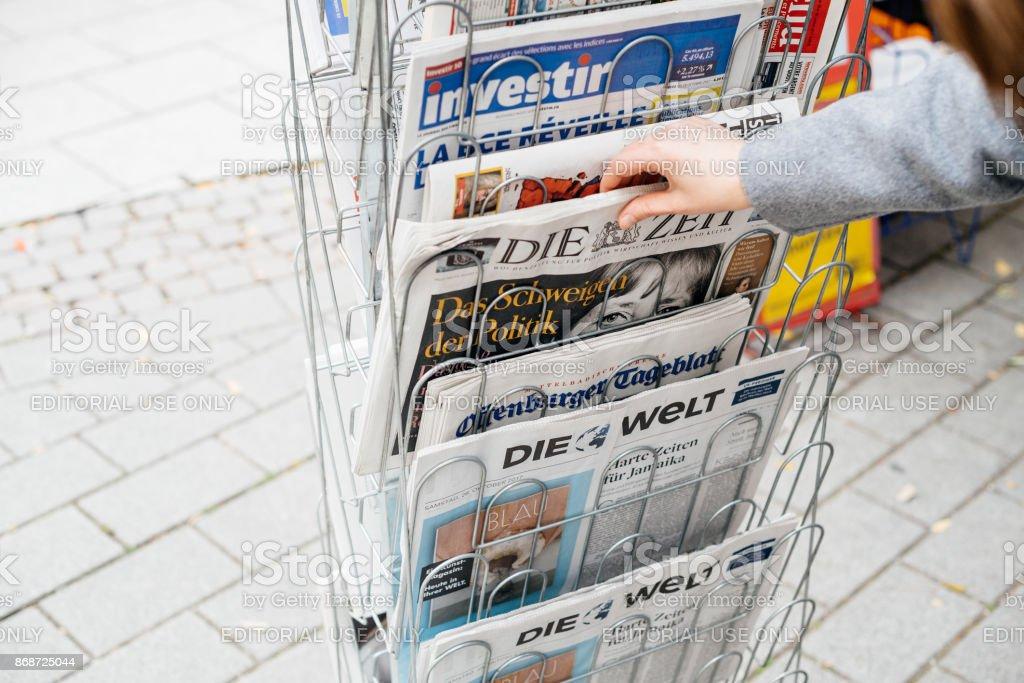 Woman buying German Die Zeit newspaper with Angela Merkel stock photo