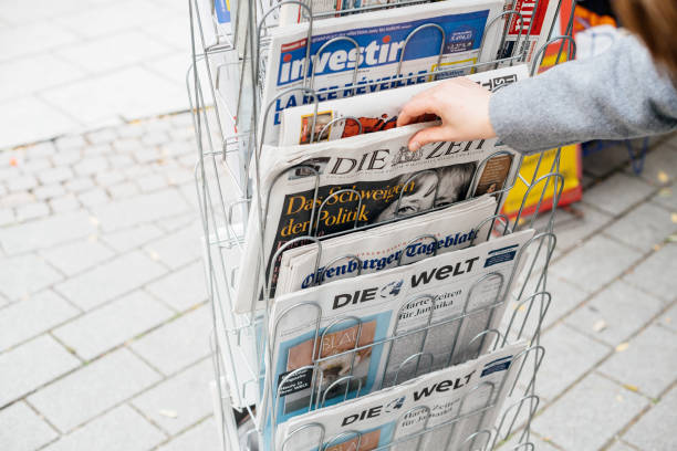 Woman buying German Die Zeit newspaper with Angela Merkel Strasbourg: Woman reading buying German Die Zeit newspaper at press kiosk featuring Angela Merkel and tilte The Silenece of Politics news stand stock pictures, royalty-free photos & images