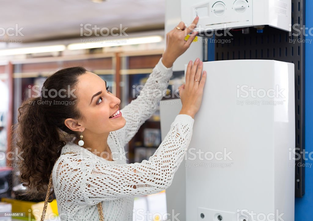 Woman buying heating water boiler stock photo