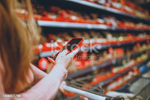 Woman looking on the shopping list using smartphone while shopping in the supermarket