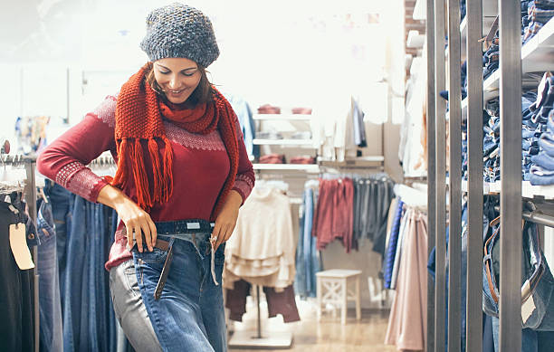 woman buying jeans at retail store. - jeans stock photos and pictures
