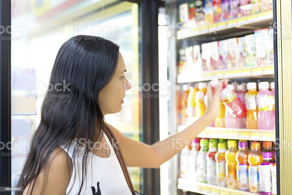 Woman buying juice in the store stock photo