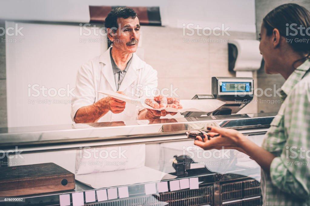 Frau bei der Metzgerei Fleisch kaufen – Foto
