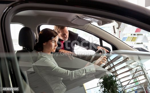 1049198210 istock photo woman buying new car from salesperson 483691595