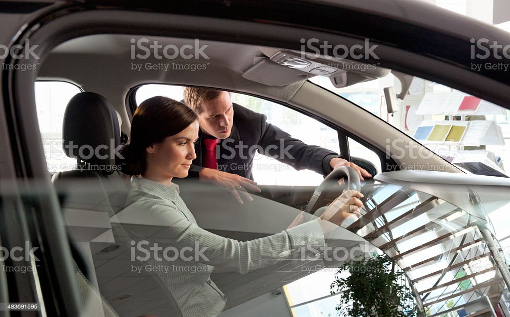 woman buying new car from salesperson stock photo