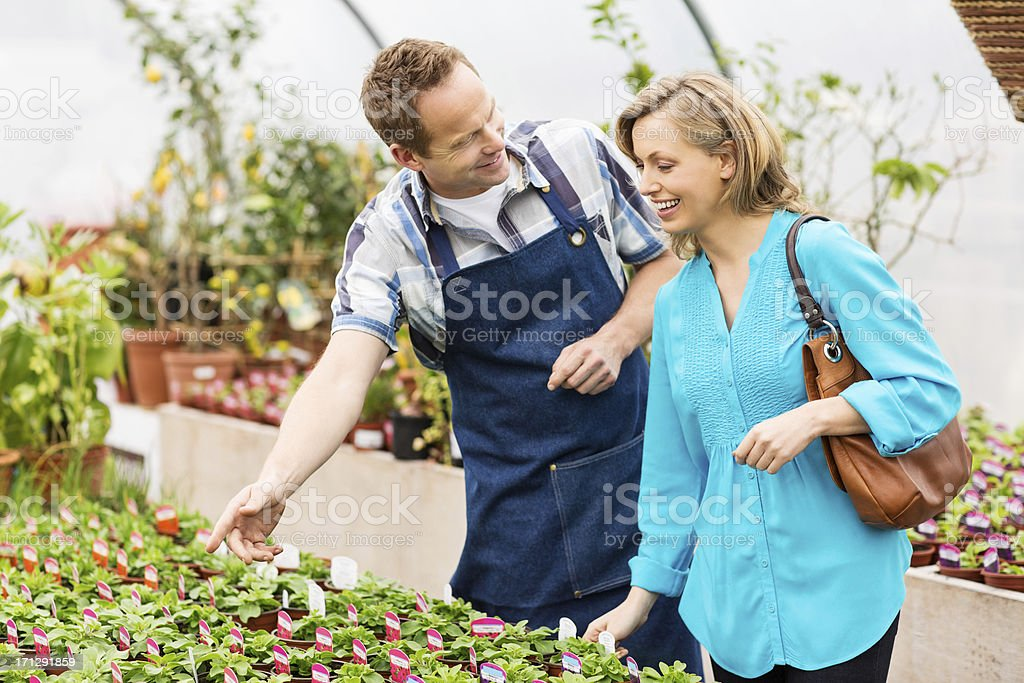Woman Buying Potted Plants At Garden Center royalty-free stock photo