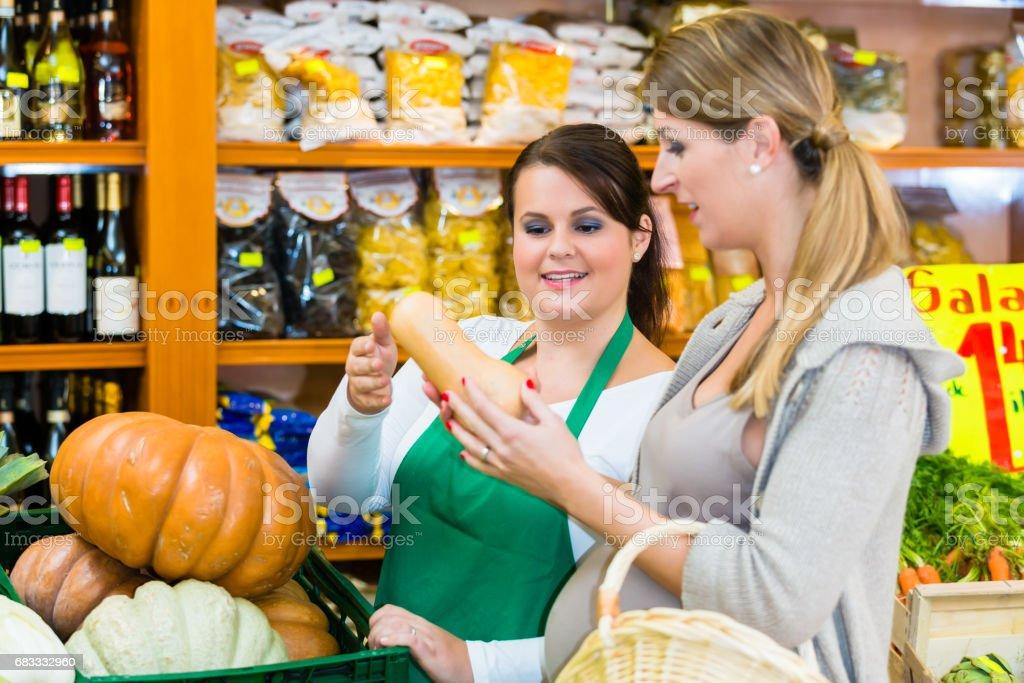 Femme achat potiron et légumes en épicerie fine photo libre de droits