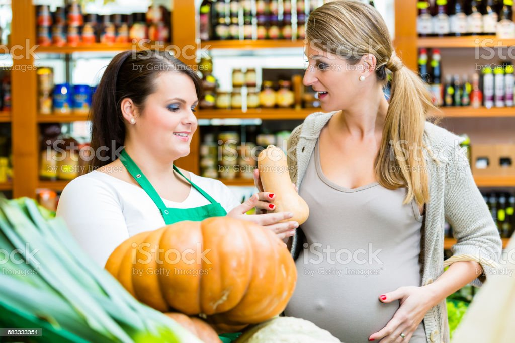 Woman buying pumpkin and vegetables in delicatessen royalty-free stock photo