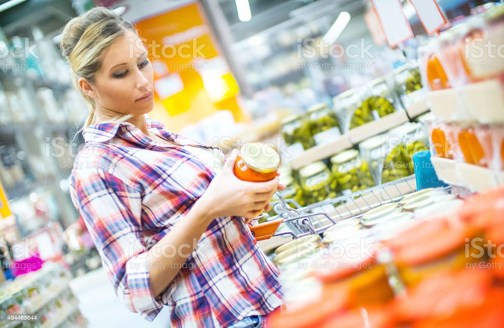 Woman buying some pickled vegetables in supermarket. stock photo
