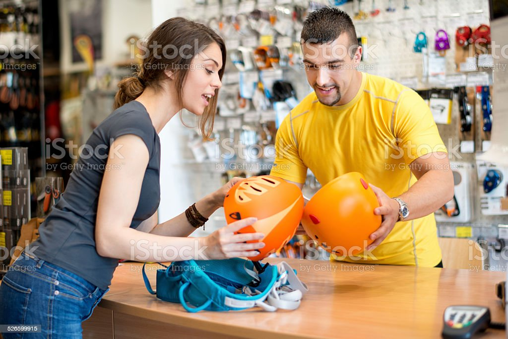 Woman buying sports helmets in the store stock photo