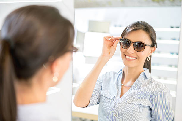 woman buying sunglasses at the optician's shop - 자외선 차단 뉴스 사진 이미지