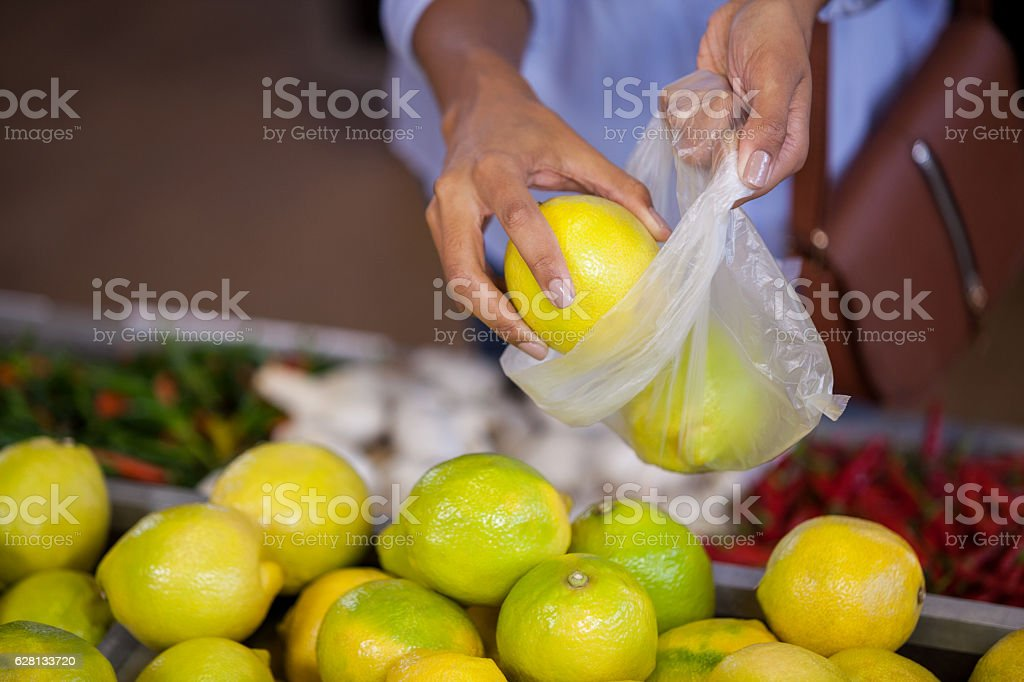 Woman buying sweet lime stock photo