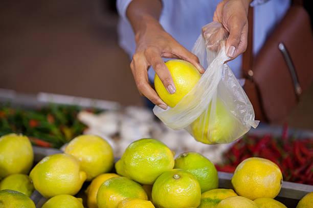 woman buying sweet lime - sac en plastique photos et images de collection