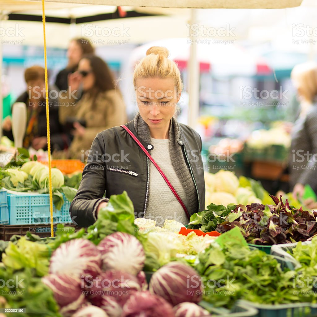 Woman buying vegetable at local food market. stock photo