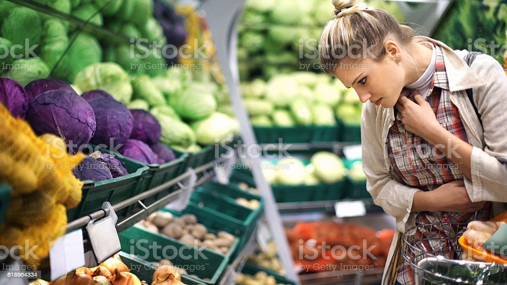 Woman buying vegetables at a supermarket. stock photo