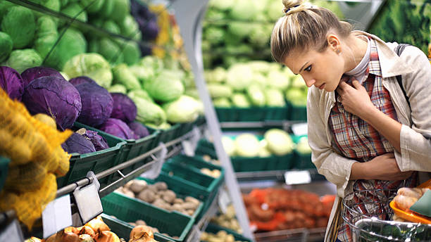Woman buying vegetables at a supermarket. Closeup of early 30's attractive blond woman buying some vegetables at a local supermarket. She's standing in front of piles of vegetables and making choices. produce aisle stock pictures, royalty-free photos & images