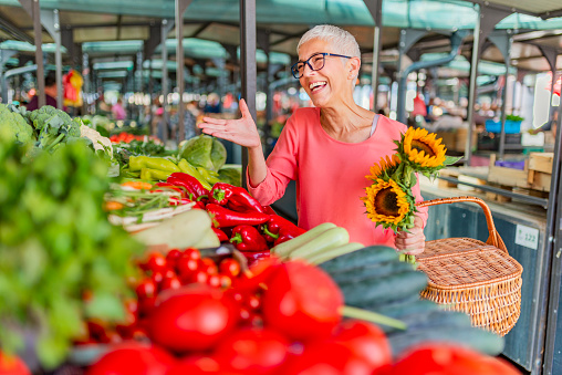 Woman buying vegetables at farmer's market stall.