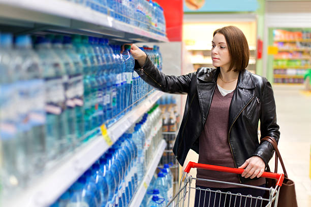 Frau kauft eine Flasche Wasser – Foto