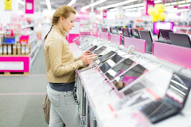 Femme achète une tablette numérique. - Photo