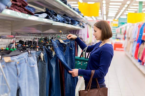 frau kauft ein paar jeans - damen jeans sale stock-fotos und bilder
