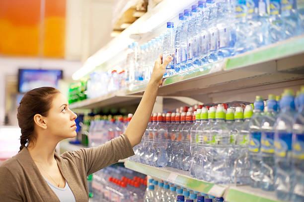 Frau kauft eine Flasche Wasser in-shop – Foto