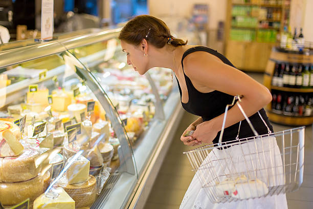 woman buys cheese in the supermarket - delis stock photos and pictures