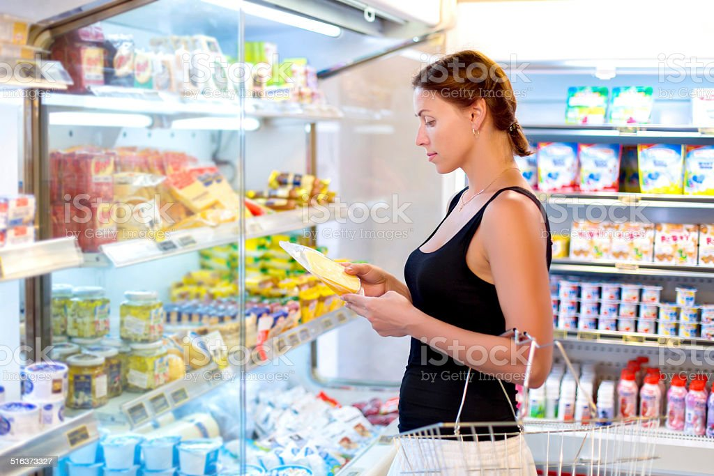 woman buys cheese in the supermarket stock photo