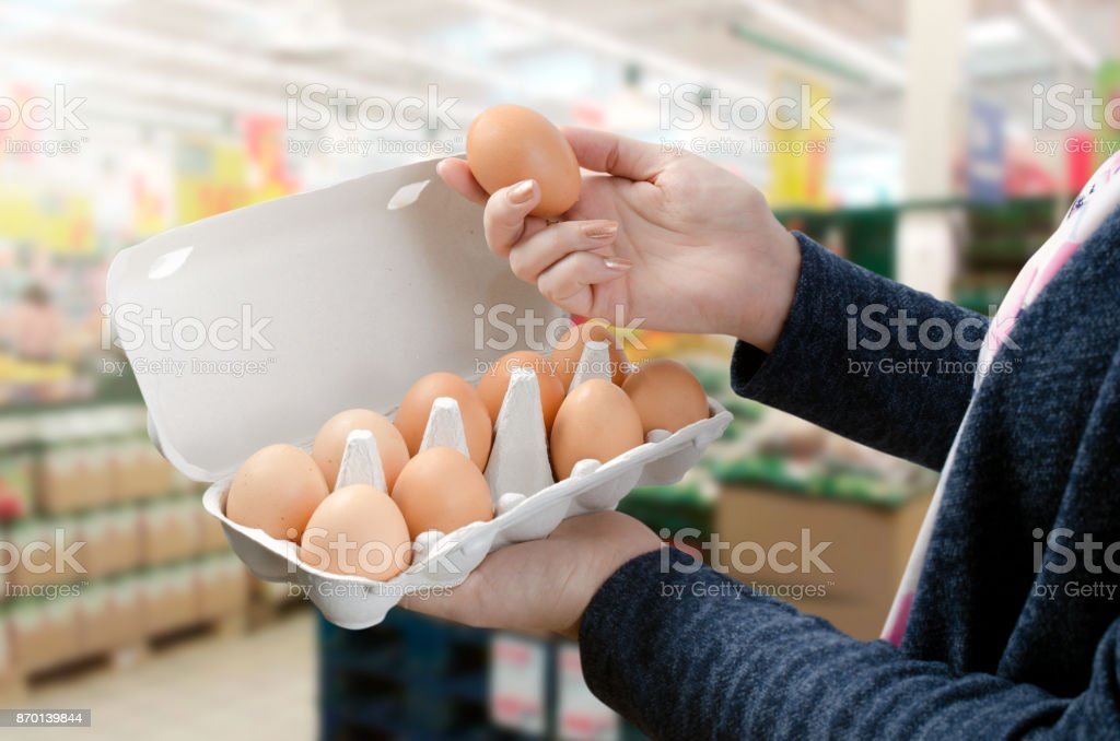 Woman buys eggs in the supermarket stock photo