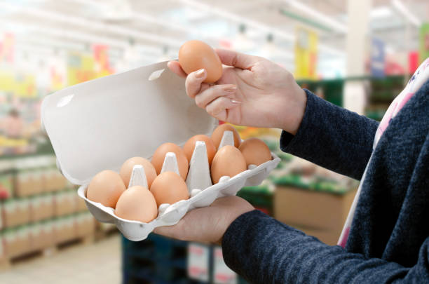 woman buys eggs in the supermarket - uovo foto e immagini stock