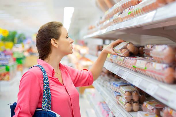woman buys eggs stock photo