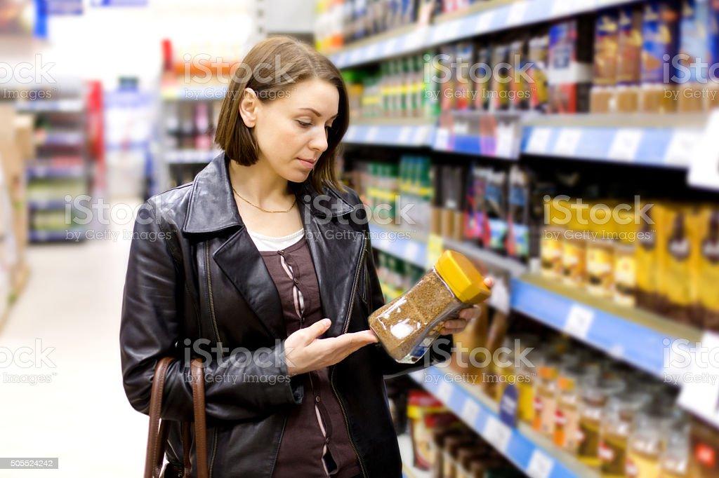 Frau kauft im Supermarkt Kaffee – Foto