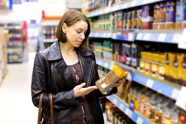 woman buys in the supermarket coffee stock photo