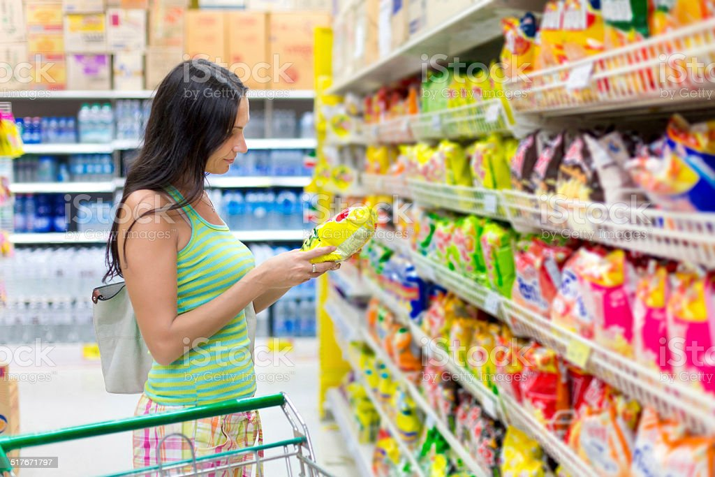 Woman buys potato chips in the store stock photo