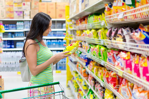 Woman buys potato chips in the store Woman buys potato chips in the store snack aisle stock pictures, royalty-free photos & images