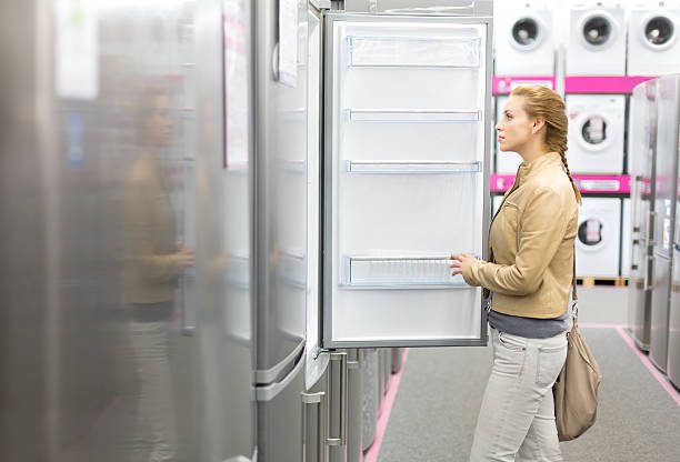 woman buys the refrigerator in shop. stock photo