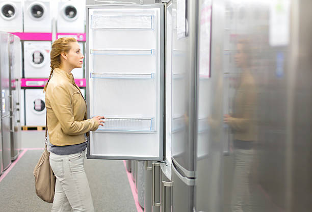 woman buys the refrigerator in shop stock photo